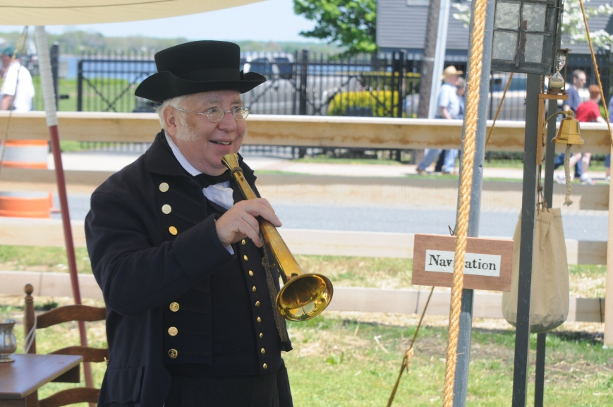 A ship's navigator, working a tent over by the Lighthouse Museum, explains an array of instruments used on the ship.