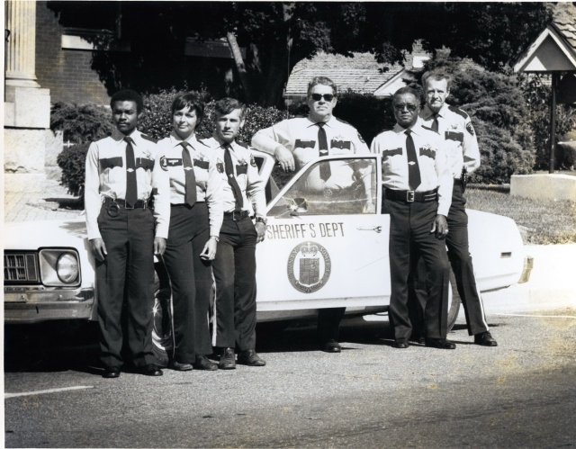 The Somerset County Sheriffs Office in the early first half of the 1980s.  Deputy Bobby Jones is the third from the left and Sheriff Foxwell stands behind the door.